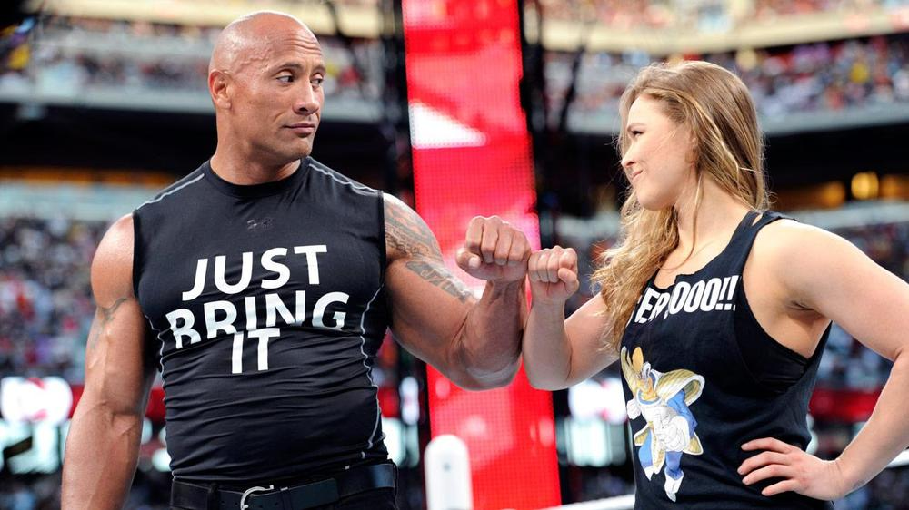 WWE Superstar The Rock and UFC Women's Bantamweight Champion Ronda Rousey fist bump inside the WrestleMania 31 ring.