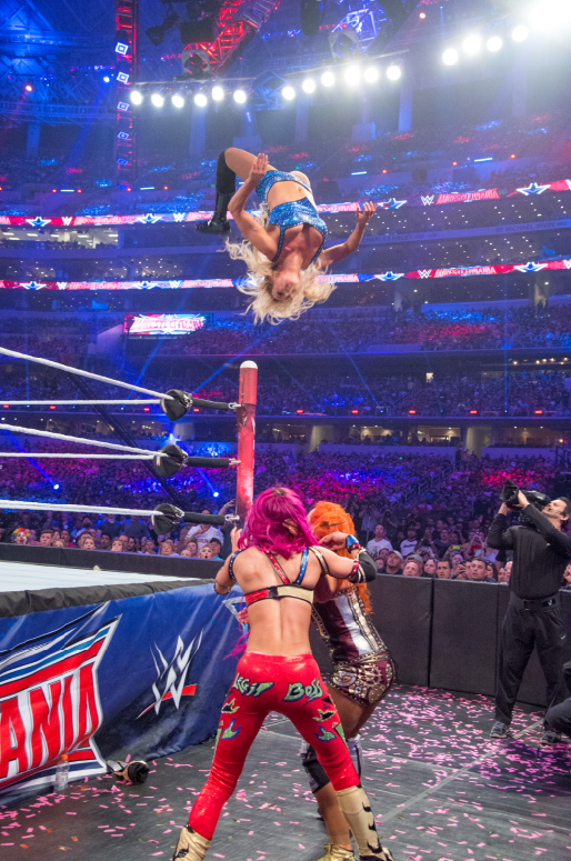 Charlotte flies through the air with a moonsault onto opponents Sasha Banks and Becky Lynch in the Women's Championship Match at WWE WrestleMania 32.