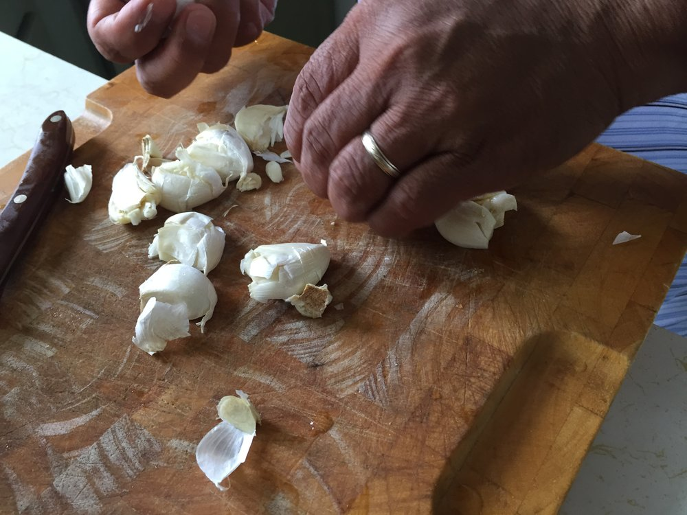 My dad chopping up some garlic. These add a great aroma and taste to the meat.