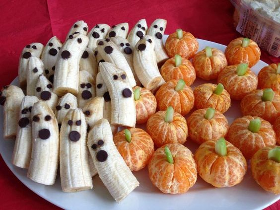 Halloween food and decorations. Banana ghosts and mandarin pumpkins with celery stems. Image Source: Pinterest