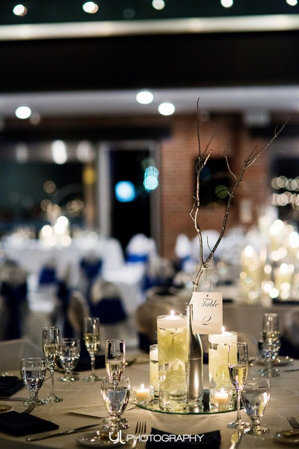 Centerpieces made out of spray painted San Pellegrino bottles and branches.