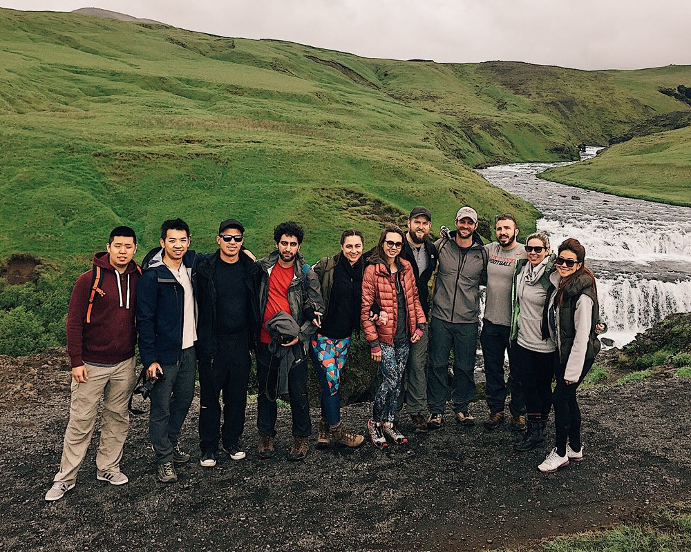 Partial group photo at Skogarfoss. Volcano in the background. Falls in the background. Beautiful people in the foreground.