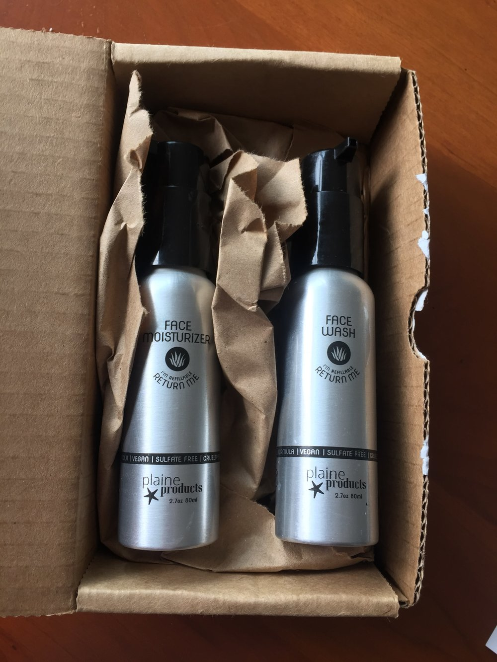 Plaine Products Face Wash and Moisturizer in aluminum container with plastic caps. Refillable and comes in plastic-free packaging.