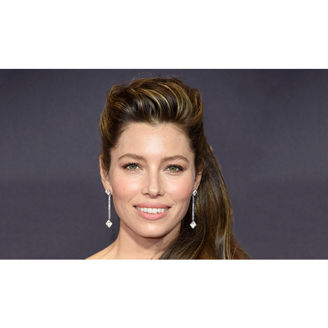 1960's Inspired Voluminous Waves styled with Virtue. JESSICA BIEL'S EMMYS LOOK: SEXY 60'S CASCADING WAVES Apply Virtue Uplifted Volumizing Whip at the roots of damp hair for volume and hold. Follow up with Virtue Perfect Ending Split End Serum to mend ends and create a glossy finish. Blow-dry the hair as usual; once hair is dry, use a 1.25'' curling iron to set hair in barrel curls then brush out when cool for soft glamorous waves.   For lift, backcomb the roots and set hair with Virtue Finale Shaping Spray.   To finish the look, lift hair into a half up style and secure with pins and allow the rest to cascade down onto one side.