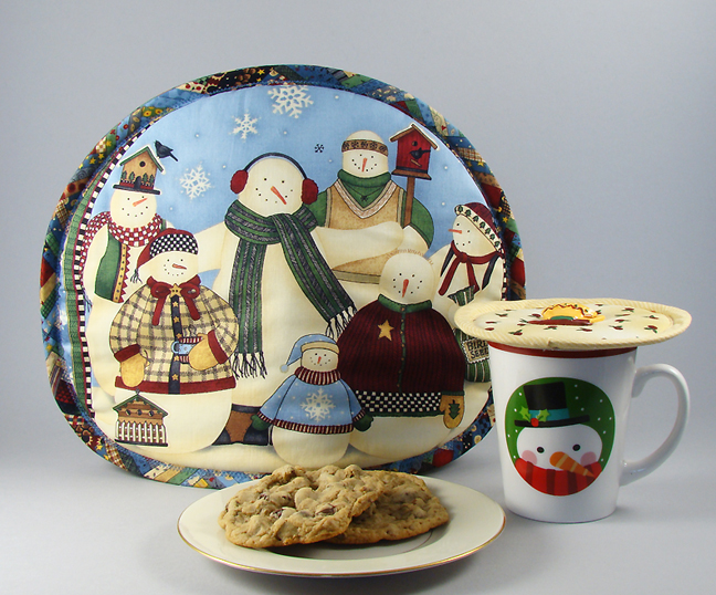 Thinsulate insulated Snowmen Family Reunion Tea Tabard on a teapot.                  Thinsulate insulated Rosebud Rhapsody Kup Kap on holiday mug.