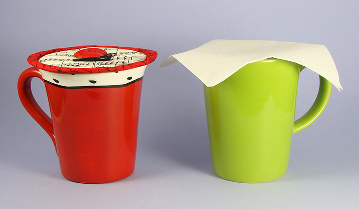 Thinsulate insulated Music Krescendo Kup Kap on large red mug. Useless paper napkin on green mug.