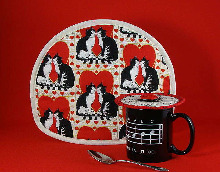 Thinsulate insulated Tuxedo Kats Tea Tabard over a tea pot; Music Krescendo Kup Kap on mug.
