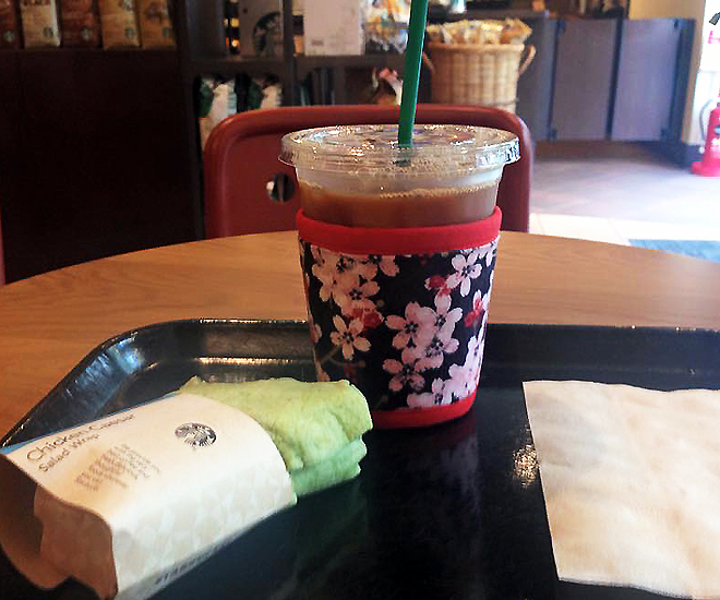 Interesting iced coffee and salad wrap sandwich at Starbucks in Tokushima, Japan, with  Cherry Blossoms Kup Kap coffee sleeve  by Koffee Kompanions keeping ice from melting in the plastic coffee container.
