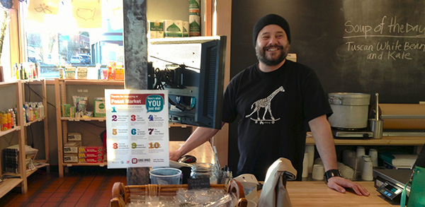 Owner of Feast Market in downtown White Salmon proudly displays a poster designed by Blue Marble Creative for GO!, reminding customers of 10 reasons why local ownership matters.