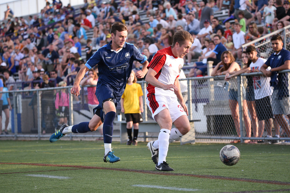 Vaughan challenges a Michigan Stars defender for possession, last year at Hollway Field