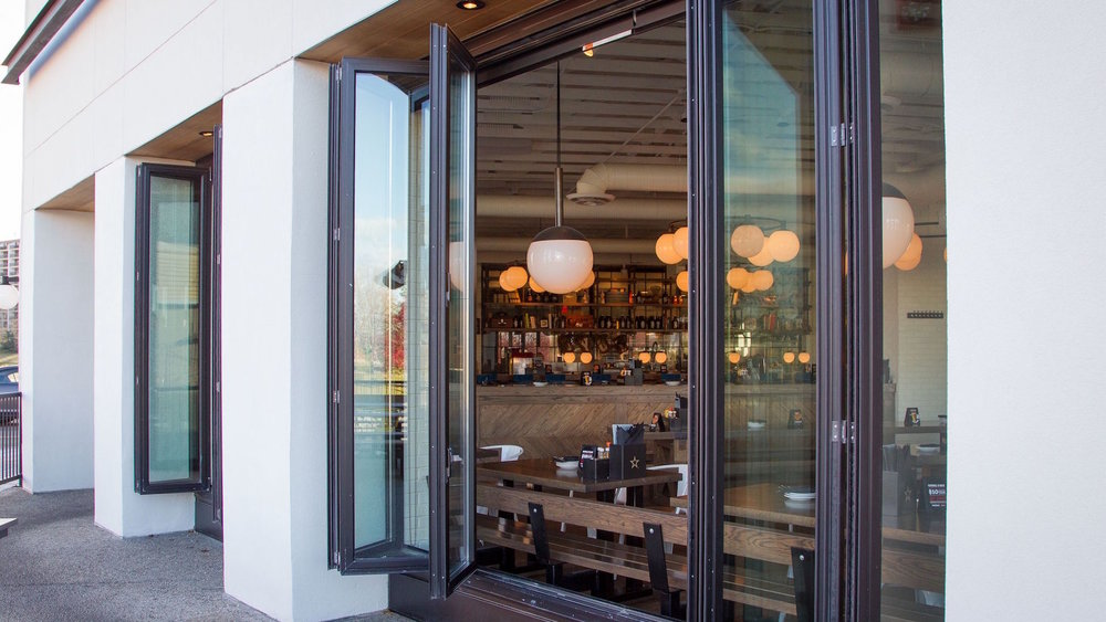 Folding doors and windows   To allow wider panels with maximum glass and keep the costs reasonable, we use a folding door system that holds the weight of the panels on the sill. The system can stack left or right, inside or outside and can have an integrated door with multi-point hardware for in and out access to the barbecue or deck. It's gorgeous!