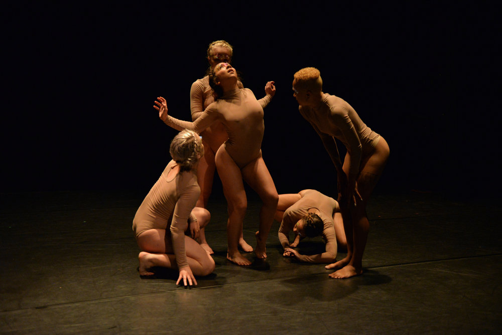 Four dancers examining one in the center, photo by Jessica Schmitt. Photo from the 11th Annual REVERBDance Festival.