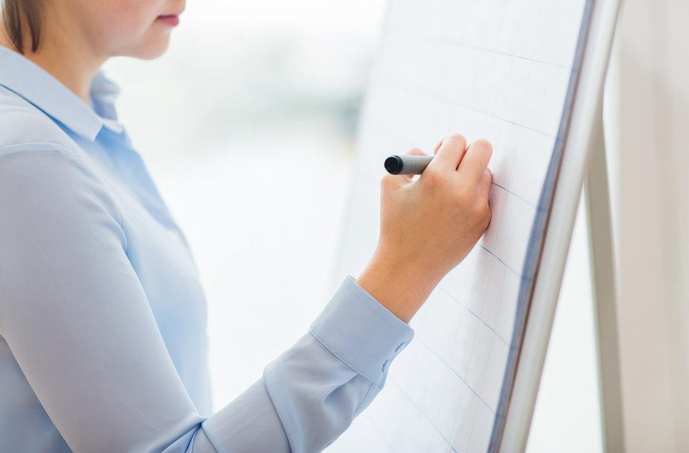 close-up-of-woman-writing-something-on-flip-chart-PTFSZY2.jpg