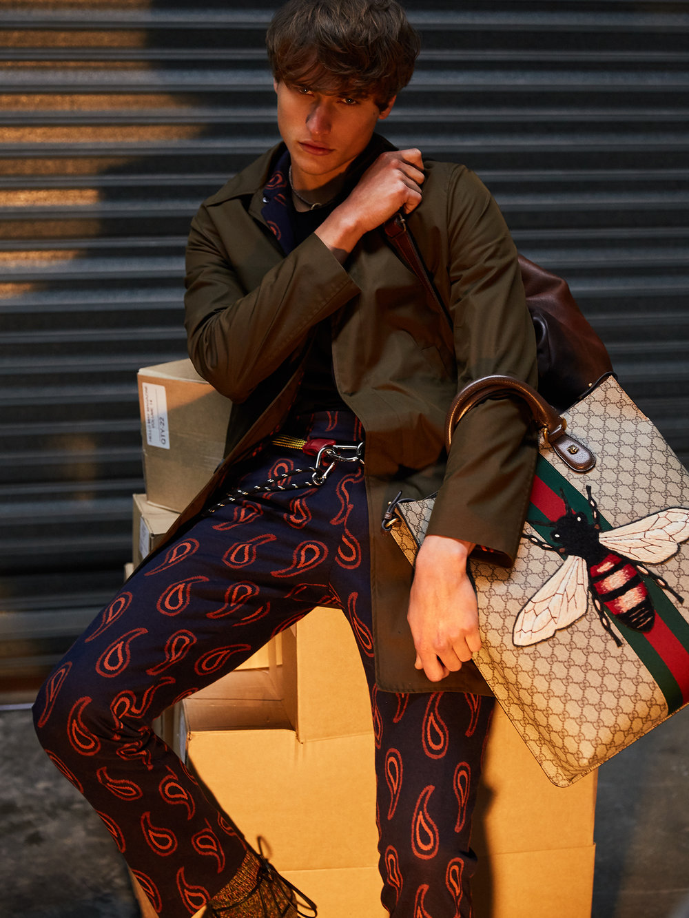 Coat – PS by Paul Smith, Jacket and pants – Paul Smith, T-Shirt – Kit & Ace, Backpack – Hunt Leather, Bag – Gucci, Necklace – stylist's own, Rope belt – stylist's own, Sandals – Gucci, Socks – stylist's own.