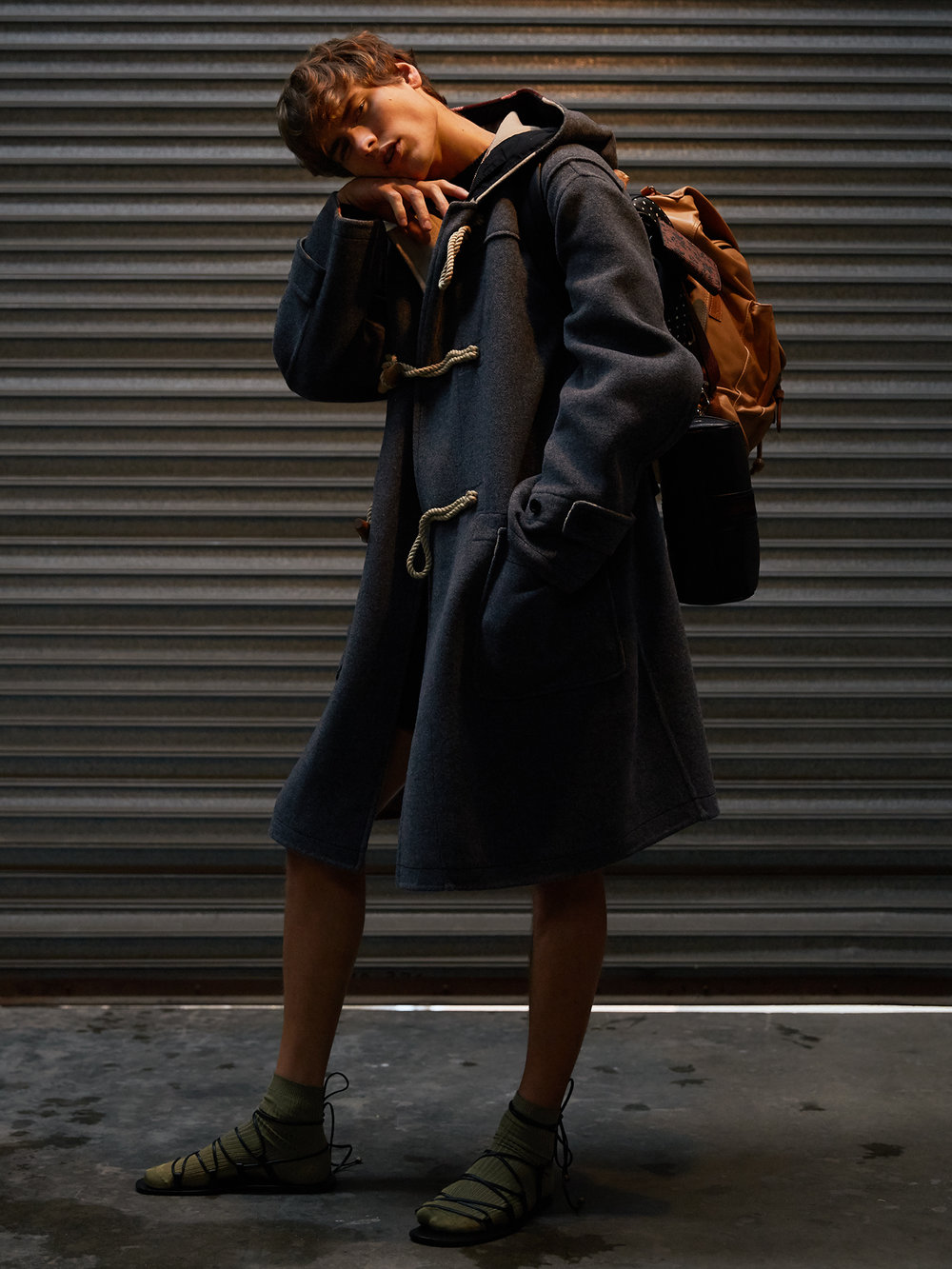 Coat – Burberry , Jumper – Salvatore Ferragamo, Backpack (black & white) – Coach, Backpack (tan) – Hunt Leather, Pouch – Paul Smith, Wallet (floral) - Paul Smith, Necklace – stylist's own, Sandals – Gucci, Socks – stylist's own.