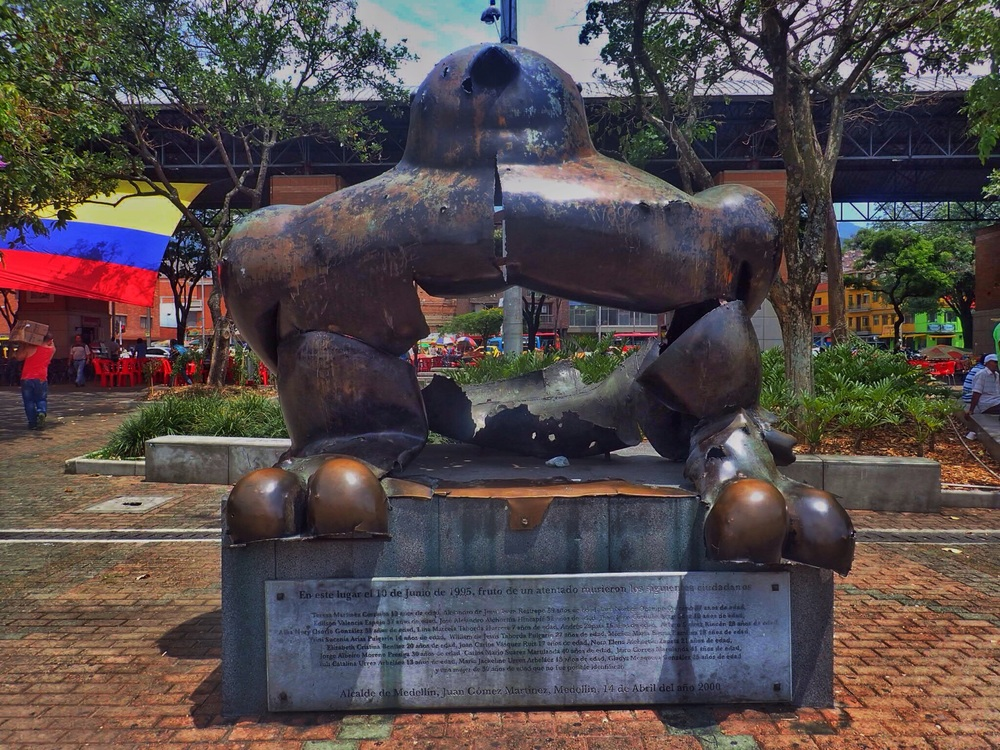 A statue still standing despite an explosion is a reminder of Colombia's past and how far the country has come.