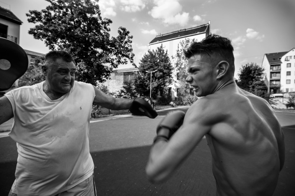 """Ghetto Balboa - Director: Árpád Bogdán    This film follows a boxing coach and his trainee from the very beginning to the first successes. Both characters are of Roma origins from the infamous Ghetto in the middle of Budapest. Misi Sipos is an ex-member of the 8th district mafia who turned to God and left behind his criminal past. As his personal """"mission"""" he started a local community boxing club aimed at young children from troubled families. Zoli Szabó is one of these kids who, despite his young age, has to face up to the responsibility of providing for his family. He has a tough decision to make, as he either becomes a professional boxer, which comes with a lot of sacrifices or he follows in the footsteps of his mobster father."""
