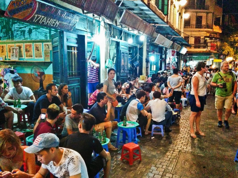 A busy street lined with street food vendors in Hanoi.   Courtesy: Foodaholix
