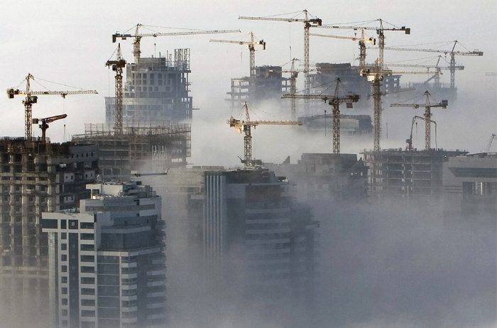Cranes peek through the fog in Dubai.   Courtesy: imthy.com