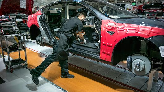 A worker assembles a car at Tesla's Fremont plant.   Courtesy: CNBC