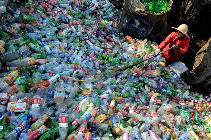 A Chinese worker piles up the plastic bottles collected at a recycling center in Hefei.   Courtesy: Asia Society