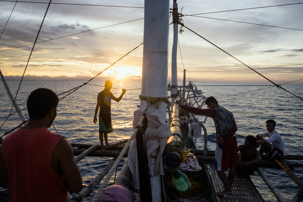 Kalibo, Philippines - September 21, 2015: The crew of a local fishing boat heads out for their night's catch. Members of the crew, who make approximately 35 USD per month, have expressed their desire to work on a larger fishing vessel for the promise of a higher income despite stories of fellow fishermen about the forms of abuse that happen on such vessels. Hannah Reyes