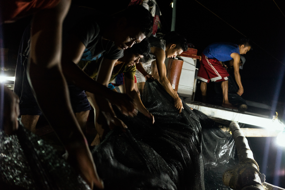 Kalibo, Philippines - September 21, 2015: The crew of a local fishing boat fish for their night's catch. Members of the crew, who make approximately 35 USD per month, have expressed their desire to work on a larger fishing vessel for the promise of a higher income despite stories of fellow crewmembers about the forms of abuse that happen on such vessels. Hannah Reyes
