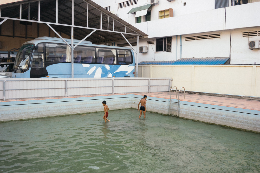 Two boys cool off after training at a mossy pool in a gym in Phnom Penh.
