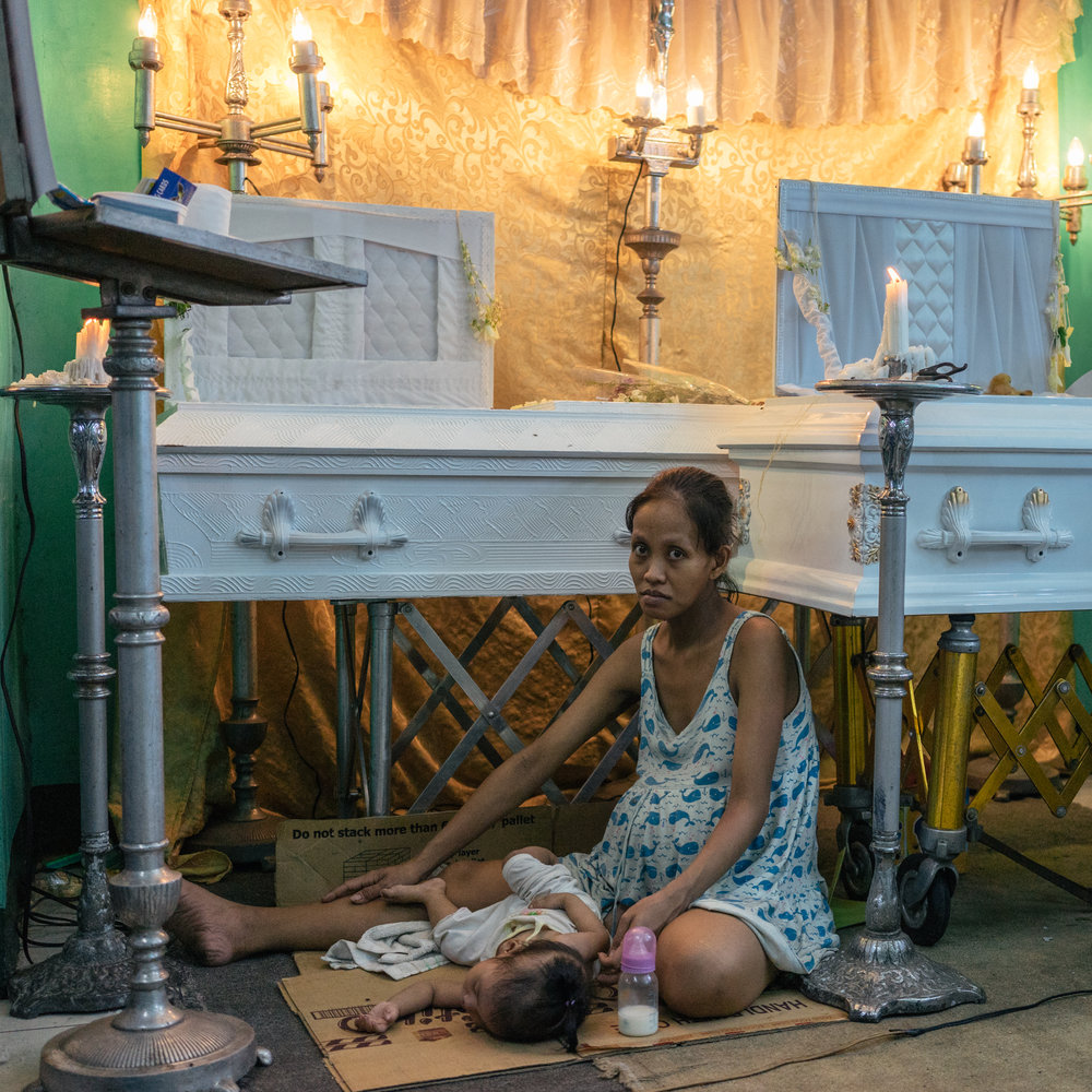 Elizabeth Navarro, 9 months pregnant, sits by the coffins of her partner, Domingo Manosca, and her son Francis, 6 years old. Both were shot at home.