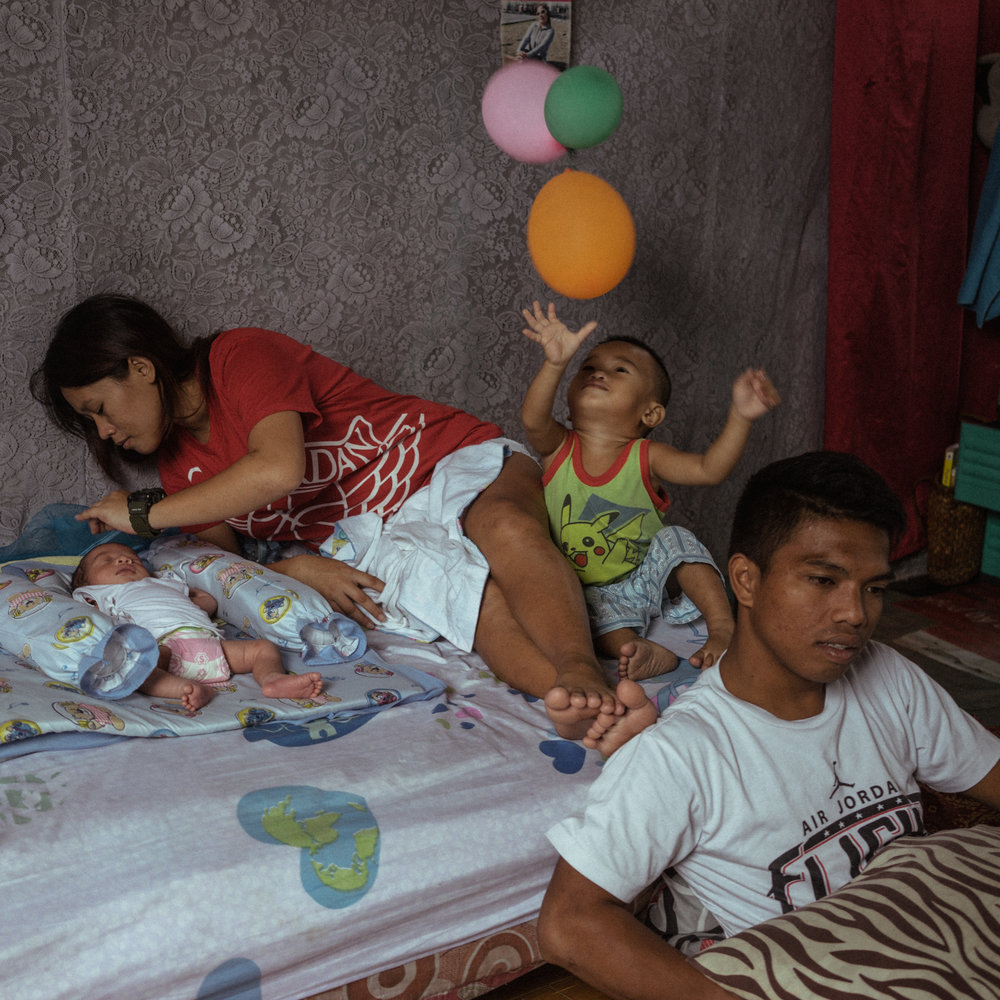 Jerome Clemente (right) is seen at the home their brother built a week after their newborn was released from the hospital. Jerome named his newborn child 'Jhay Lord' after his brother who died from Rodrigo Duterte's bloody war on drugs in the Philippines.