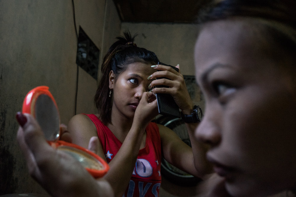 Sisters Gemma and Jojo do their make up before a night at work in Angeles City, notorious for its sex tourism. During Gemma's first night of work, Jojo gifted her little sister pepper spray and a knife. The sisters wept. In the wake of typhoons, women and girls from climate change vulnerable areas, particularly Samar and Leyte, wind up in the sex trade after being displaced from storms.