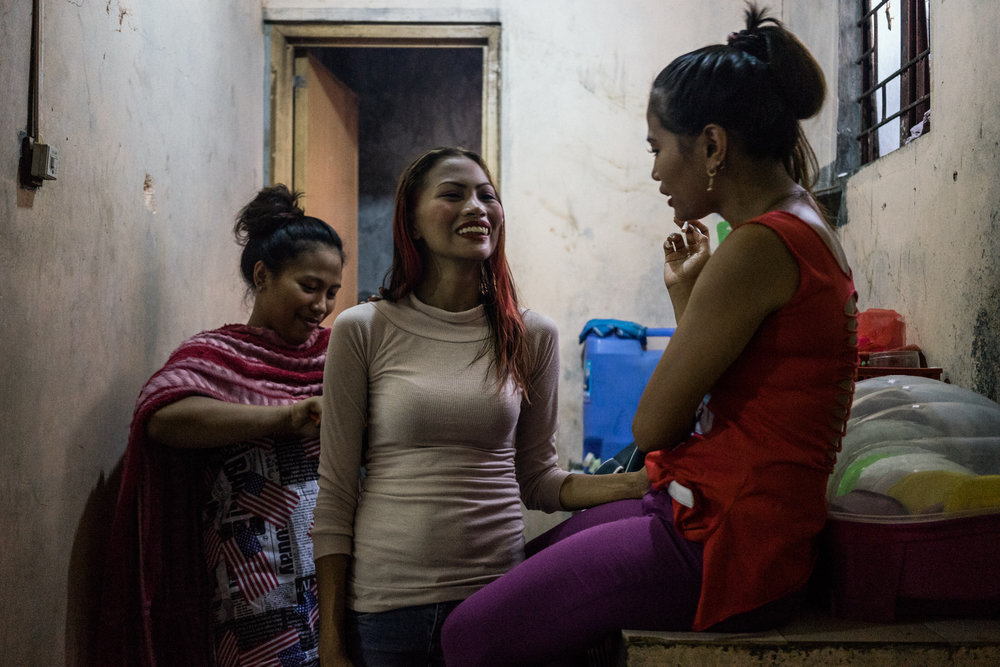 Jojo (center), Gemma (right), and Joanne (left) get ready for a night of work in the bars in Angeles City. Angeles City is known as the 'Supermarket of Sex' in the Philippines, and many of the women who work there, such as Jojo, Gemma and Joanne are from climate vulnerable areas such as Samar and Leyte.