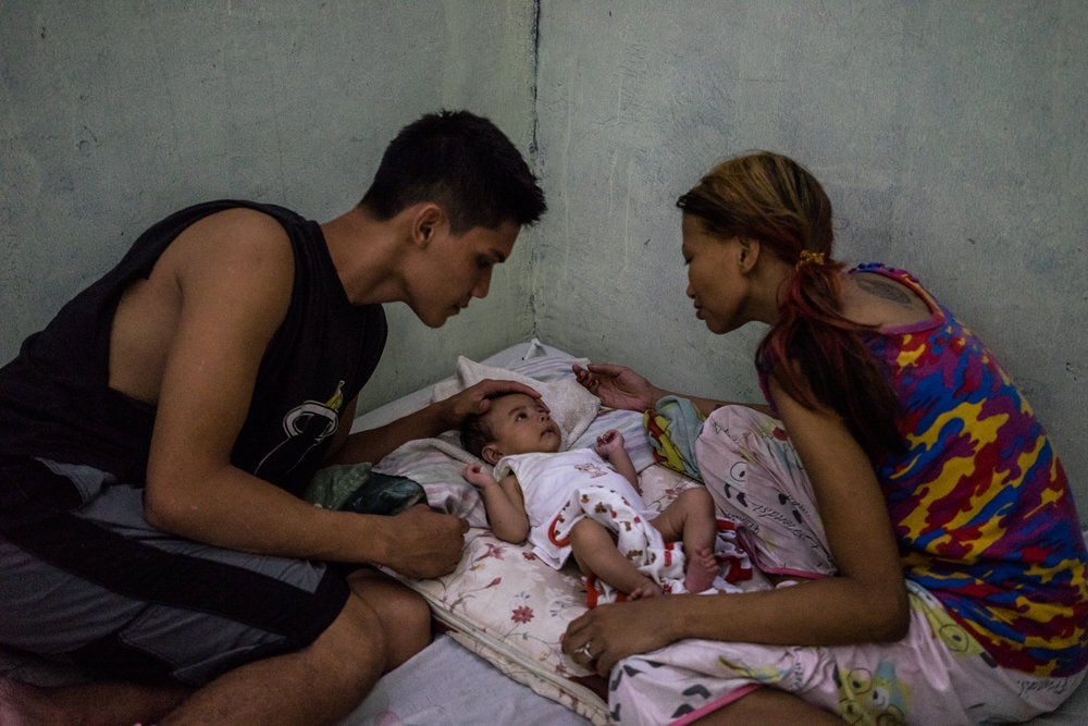 Filipina sex worker Jojo and her husband dote over their new child in their home in Angeles City. He is a stay at home dad.