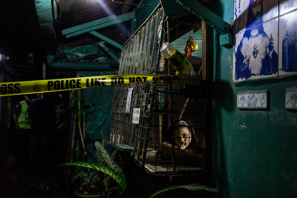 A Filipino child looks on as police tape sections off her neighbor's house after a drug related killing in her neighbor's bathroom.