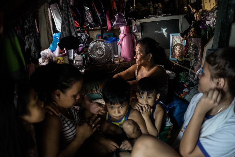 The family of Jerry Estreller Jr. are seen in their home on Tuesday April 10, 2017, in Metro Manila, Philippines. Jerry was killed in this room in December. Some of his relatives are Duterte supporters, but after Jerry's death, a few changed their minds. A few of Jerry's neighbors have expressed that they feel safer because of the killings, including Jerry's.