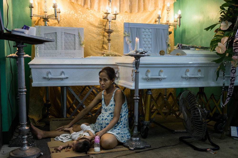 Elizabeth Navarro, 9 months pregnant, sits by the coffins of her partner, Domingo Manosca, and her son Francis, 6 years old, on Wednesday, December 14, 2016 in Metro Manila, Philippines. Both were shot at home.
