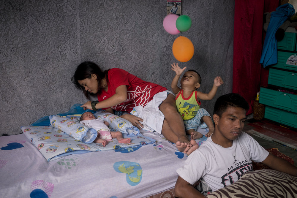 Jerome Clemente (right) is seen with his family in the home his slain brother built. Jerome named his newborn child 'Jhay Lord' after his brother who was killed from Rodrigo Duterte's bloody war on drugs in the Philippines, which has taken thousands of life since he took office.