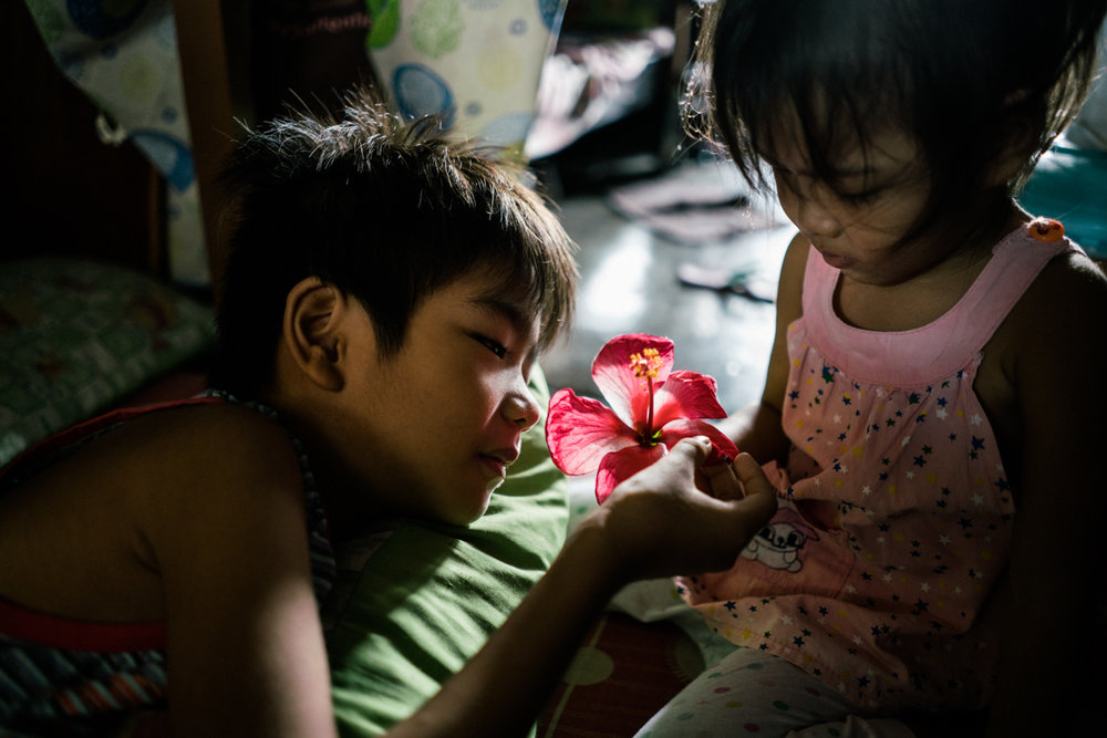 A young boy touches a gumamela flower that his sister picked from the ground. They live in a tenement in Manila where many drug deaths have taken place.