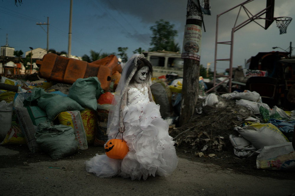 A young girl dressed as an undead bride is seen in her neighborhood, where multiple drug deaths have taken place. / Hannah Reyes Morales Photography