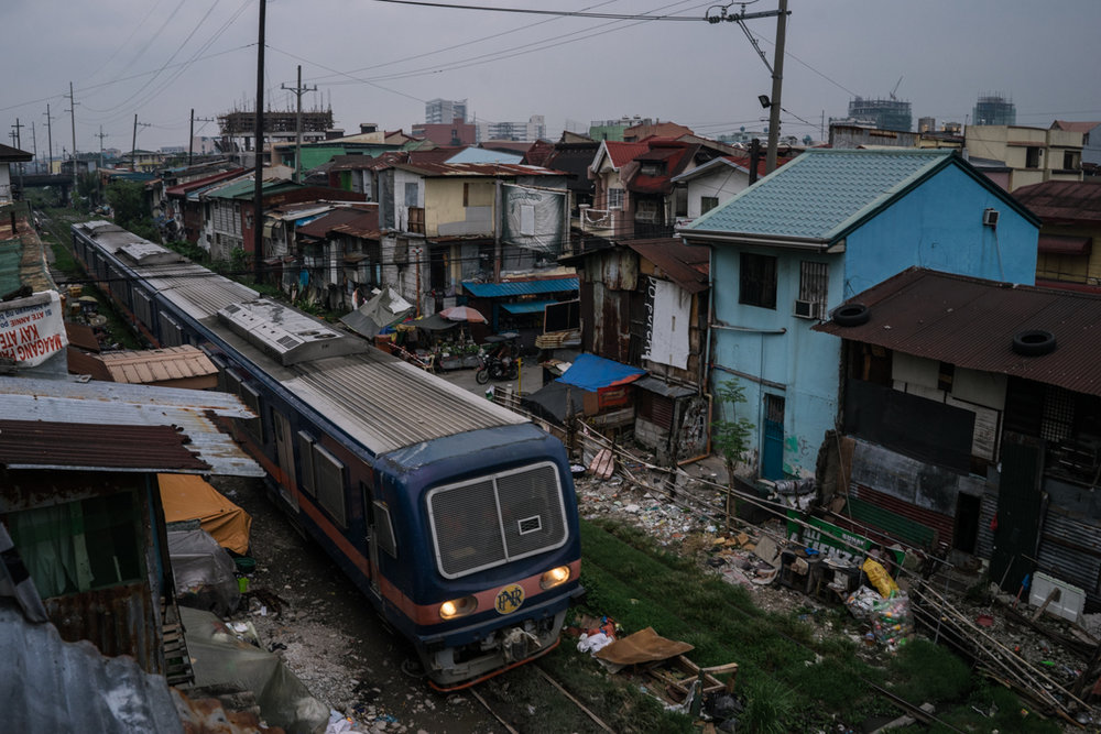 A train runs through a shanty community in Metro Manila. Many makeshift homes are built around railroads.