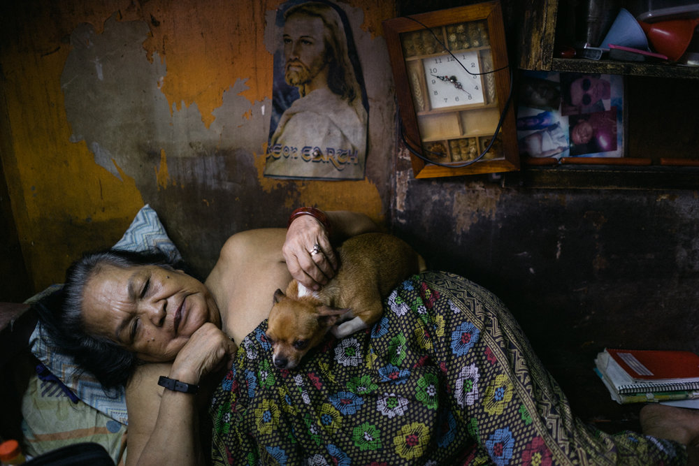 A Filipino woman and her dog are seen in their home in a shanty community in Metro Manila. Most homes religious paraphernalia in their interior.