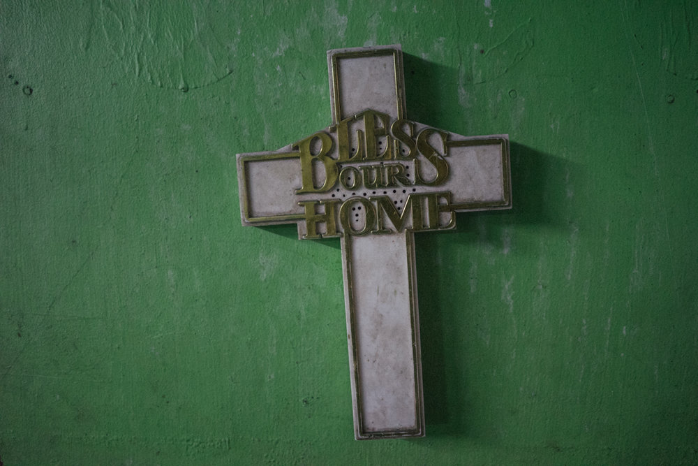 A cross saying 'Bless our Home' hangs in the wall of a home in a slum in Manila, Philippines.