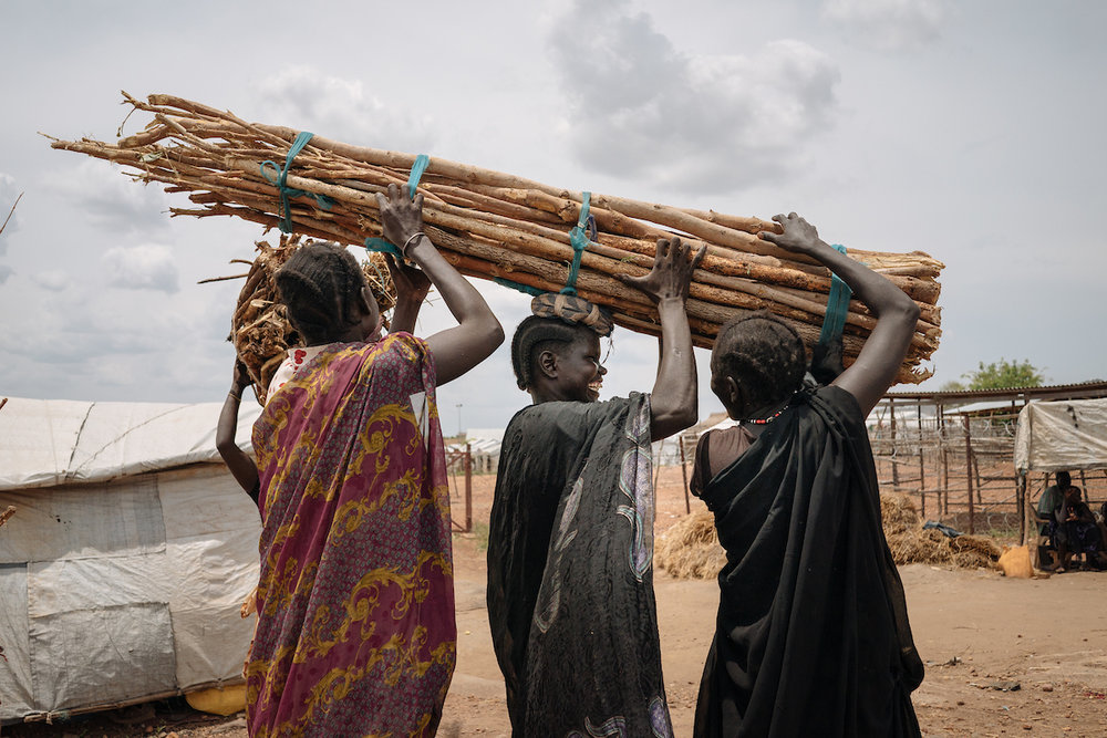 Women help each other carry firewood in Juba, South Sudan. In South Sudan, women and girls displaced from war must leave protection of civilians sites to collect firewood - a task traditionally done by women, who make up majority of the population in these camps. The journey is perilous and puts these women at continued risk of sexual violence, which rights groups have called an 'epidemic' in the country.