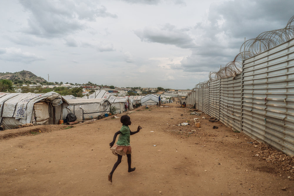 A young girl runs inside the protection of civilians site in Juba, South Sudan. In South Sudan, women and girls displaced from war must leave protection of civilians sites to collect firewood - a task traditionally done by women, who make up majority of the population in these camps. The journey is perilous and puts these women at continued risk of sexual violence, which rights groups have called an 'epidemic' in the country.