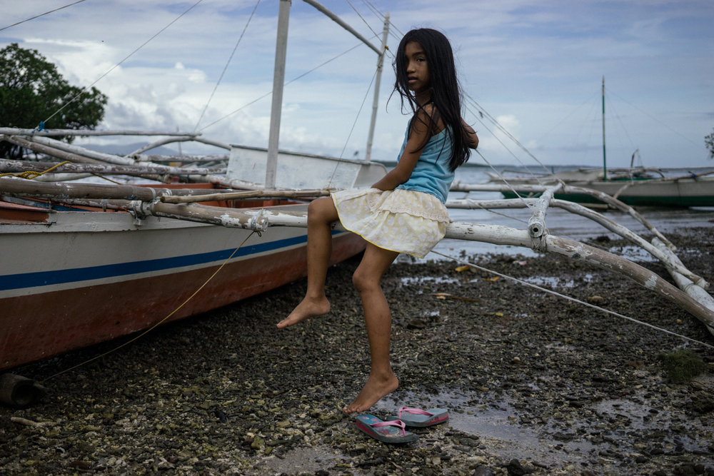 A young girl sits on a boat in a fishing village in Palawan, Philippines. Palawan is part of the Coral Triangle, the global centre of marine biodiversity, and a global priority for conservation. Over 120 million people live in the Coral Triangle, relying on it for their shelter, sustenance, and livelihood.