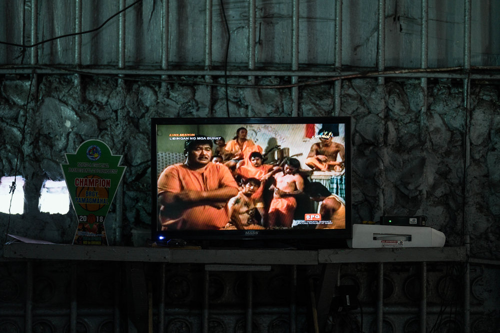 A small tv plays a movie that portrays inmates in the Manila City Jail in Manila, Philippines on October 31, 2018. In the Philippines, men with pending cases spend months, sometimes years, in overcrowded cells waiting to be charged, sentenced, or tried.