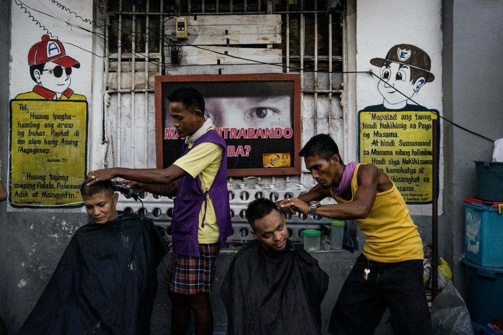 Men get haircuts inside the Manila City Jail in Manila, Philippines on October 31, 2018. In the Philippines, men with pending cases spend months, sometimes years, in overcrowded cells waiting to be charged, sentenced, or tried.