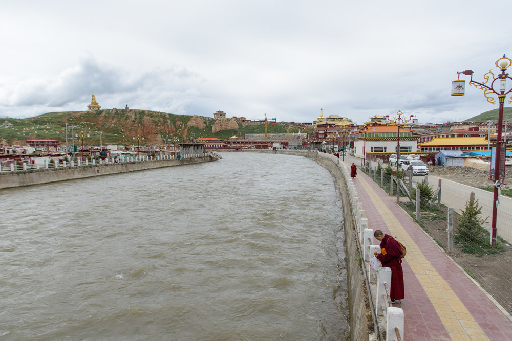 A nun throws food into the river separating the women's side of YaQing from the temple and men's neighborhood.