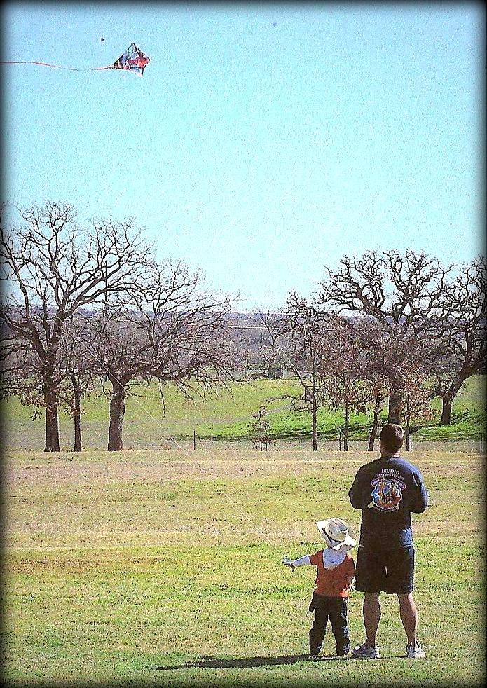 Bill and his son flying a kite.