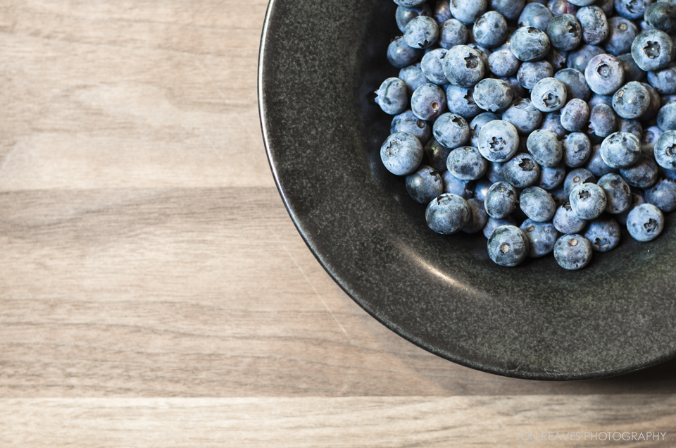 Blueberries in a bowl on a simple wooden background.